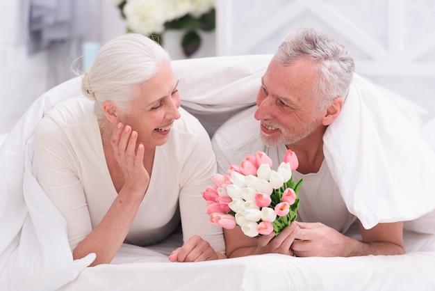 Feliz, mulher sênior, mentindo cama, olhar, tulipa, flores, segurado, por, dela, marido Foto gratuita
