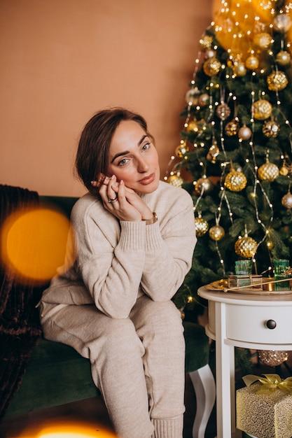Feliz mulher sentada no sofá junto à árvore de natal Foto gratuita