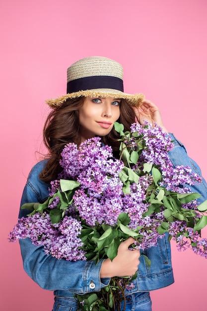 Feliz mulher sorridente no chapéu de palha posando com buquê de flores lilás Foto Premium