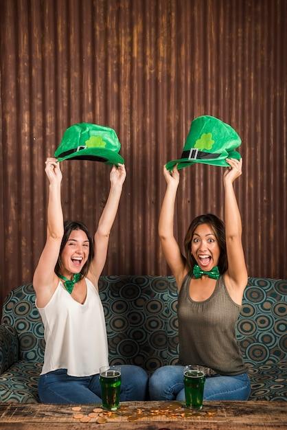 Feliz, mulheres jovens, segurando, são, patricks, chapéus, perto, tabela, com, copos, de, bebida Foto gratuita