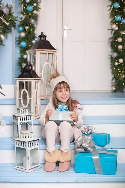 Feliz natal, boas festas! bonitinha senta-se com presentes na varanda de uma casa decorada para o natal. criança senta-se na varanda decorada para a superfície. criança abre o presente de natal. Foto Premium