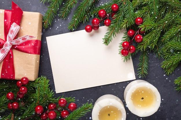 Feliz natal cartão com papel, caixa de presente, velas e galho de árvore do abeto em fundo preto. Foto Premium