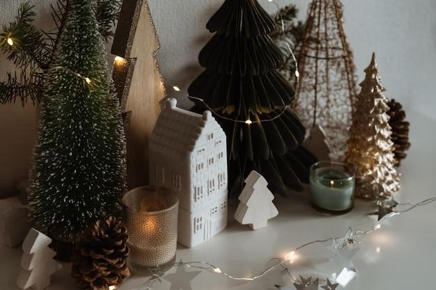 Feliz natal. casinha de cerâmica de natal, pinheiros de madeira. decorações festivas e modernas. Foto Premium