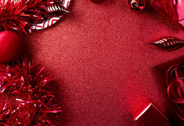 Feliz natal e ano novo fundo vermelho vista superior do ouropel, presente, bola, fita decorar na mesa Foto Premium