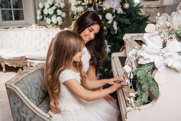 Feliz natal e boas festas. a mãe alegre e sua filha bonita no interior clássico branco, tocando em um piano branco decoraram a árvore de natal. ano novo Foto Premium