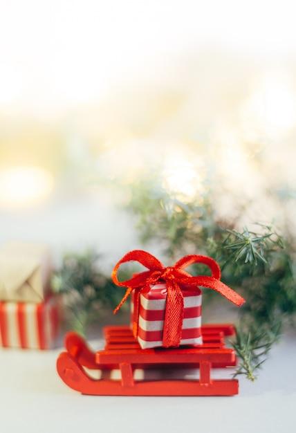 Feliz natal e boas festas cartão, moldura, banner. ano novo. galhos de árvores perenes. caixa de presente de natal em trenós de madeira. caixa com uma fita vermelha. Foto Premium