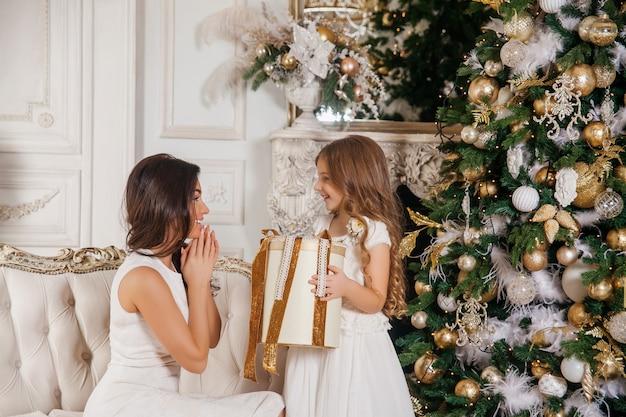 Feliz natal e boas festas. mãe alegre e sua filha linda filha trocando presentes no piano interior clássico branco e uma árvore de natal decorada. ano novo Foto Premium