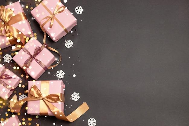 Feliz natal e boas festas padrão com presentes surpresa, fitas de atlas de ouro e neve em fundo escuro. Foto Premium