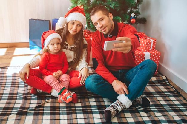 Feliz natal e feliz ano novo. jovem senta-se além de mulher e criança. ele segura o telefone e tira selfie. mulher e criança lok e pose. família usa roupas de natal e chapéus. Foto Premium
