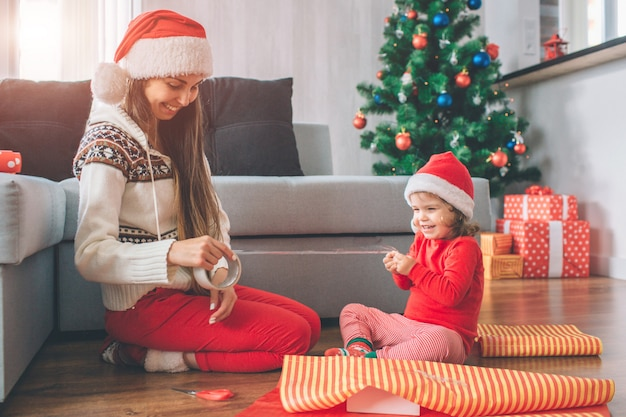Feliz natal e feliz ano novo positiva e brincalhona jovem e garota se sentar no chão. eles sorriem e riem. criança segura parte da fita enquanto a mulher tem descanso. eles usam chapéus. meninas preparam presentes. Foto Premium