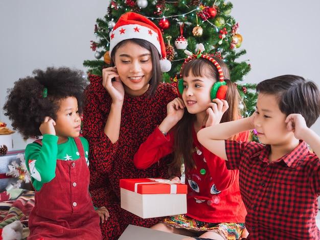 Feliz natal e feliz feriado com pessoas internacionais, crianças comemorando o natal em casa Foto Premium