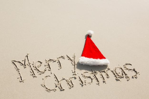 Feliz natal escrito na areia com o chapéu de santa Foto gratuita