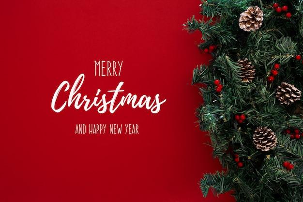 Feliz natal tópico sobre um fundo vermelho com árvore de natal Foto gratuita