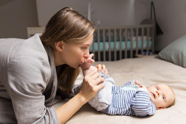 Feliz nova mãe brincalhão segurando as pernas do bebê Foto gratuita