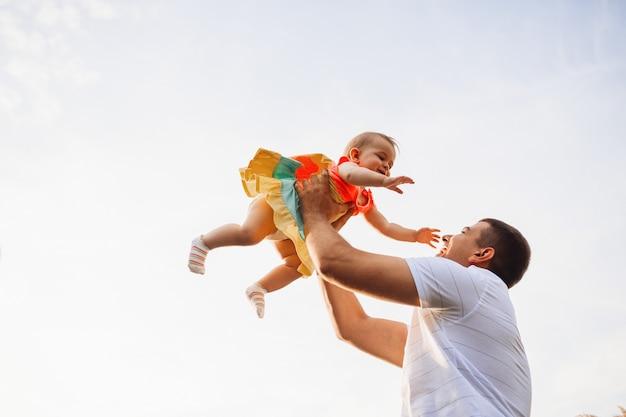 Feliz pai detém encantadora menina sob o céu de verão Foto gratuita