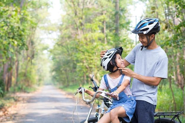 Feliz pai e filha de bicicleta no parque usa um capacete de bicicleta para sua filha Foto Premium
