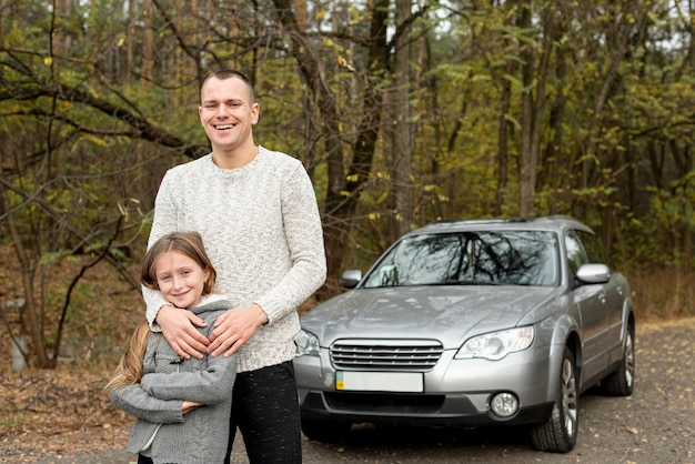 Feliz pai e filha em pé na frente do carro Foto gratuita
