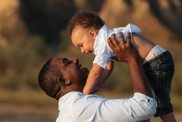 Feliz pai e filho afro-americanos se divertindo ao ar livre Foto Premium