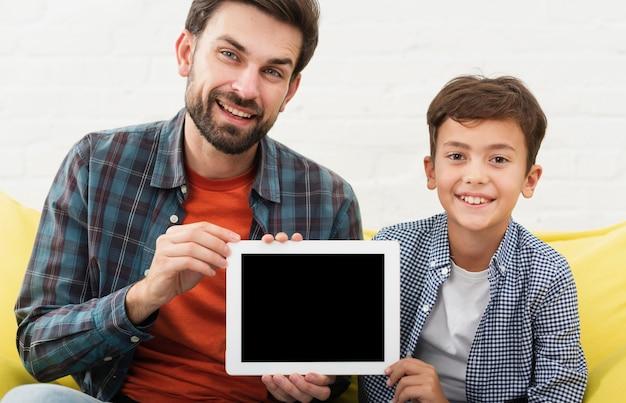 Feliz pai e filho segurando uma foto simulada Foto gratuita