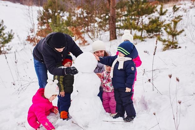 Feliz pais e filhos criam um grande boneco de neve Foto gratuita