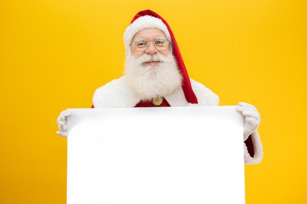 Feliz papai noel, olhando por trás do sinal em branco isolado em fundo amarelo, com espaço de cópia Foto Premium