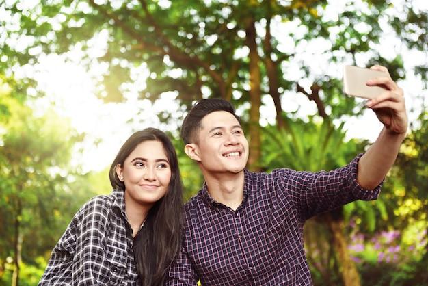 Feliz, par asiático, levando, um, selfie, com, telefone Foto Premium