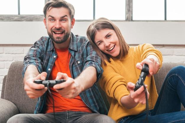 Feliz, par jovem, sentar sofá, tendo divertimento, enquanto, jogar, a, videogame Foto gratuita