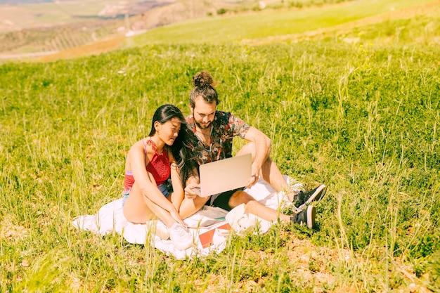 Feliz, par jovem, usando computador portátil, ligado, descanso Foto gratuita