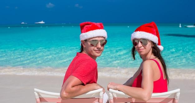 Feliz, par romântico, em, vermelho, chapéus santa, em, praia tropical Foto Premium