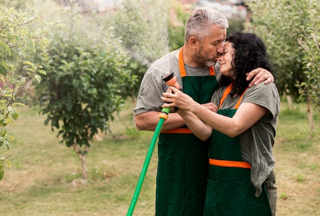 Feliz, par velho, com, mangueira água Foto gratuita