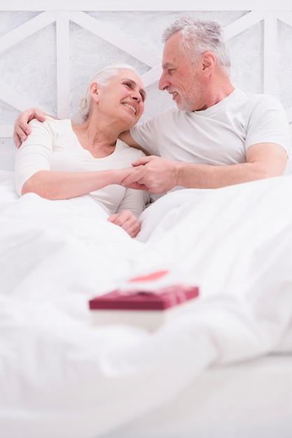 Feliz, par velho, encontrar-se cama, com, caixa presente Foto gratuita