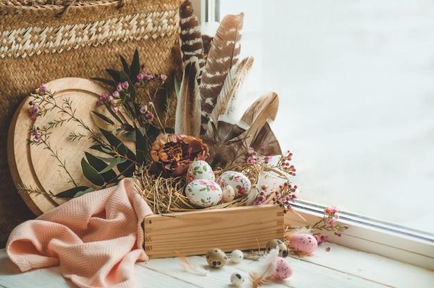 Feliz páscoa fundo. ovos de páscoa rosa em um ninho com decorações florais e penas perto da janela Foto gratuita