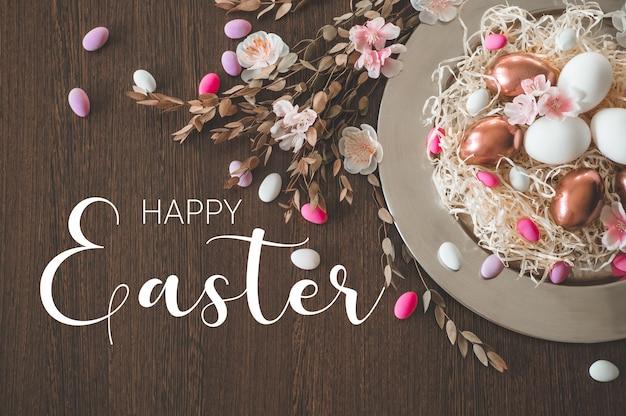 Feliz páscoa. páscoa congratulatória. ovos de páscoa em uma placa de metal com flores da primavera em um fundo de madeira. conceito de férias Foto Premium
