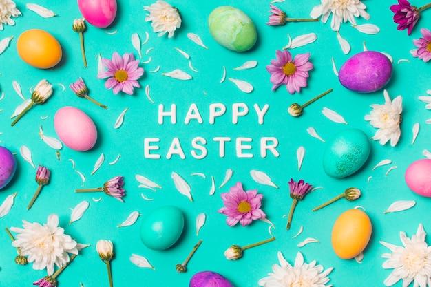 Feliz páscoa título entre ovos brilhantes e botões de flores Foto gratuita