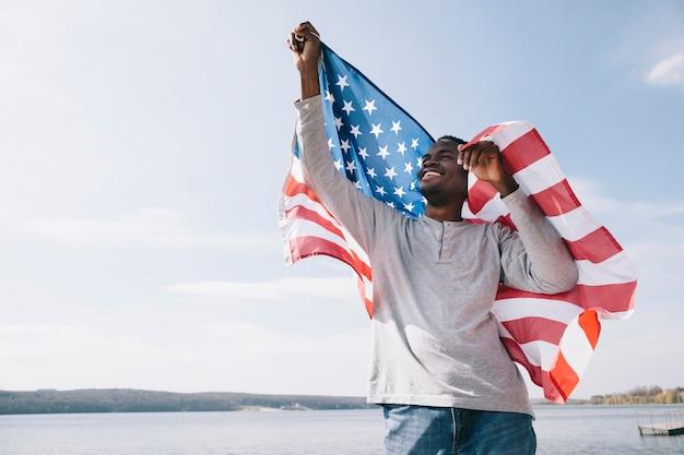 Feliz patriota americano africano segurando a bandeira dos eua Foto gratuita