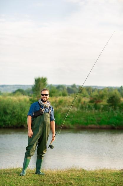 Feliz pescador com roupa especial e vara de pescar perto do rio Foto Premium