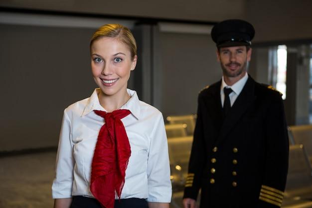 Feliz piloto e aeromoça em pé no terminal do aeroporto Foto gratuita