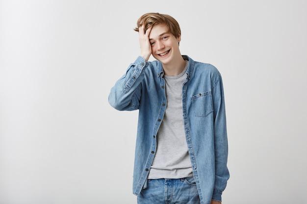 Feliz positivo modelo masculino de aparência agradável em camisa jeans e calça jeans, com cabelos loiros e olhos azuis, sorri amplamente, se sente um pouco tímido, toca seu cabelo. conceito de beleza e juventude Foto gratuita