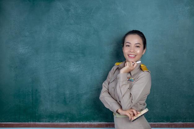 Feliz professor tailandês com roupa oficial posando na frente do quadro-negro Foto gratuita