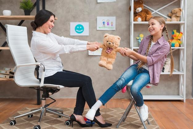 Feliz psicólogo feminino e menina jogando junto com o ursinho de pelúcia macia na clínica Foto gratuita