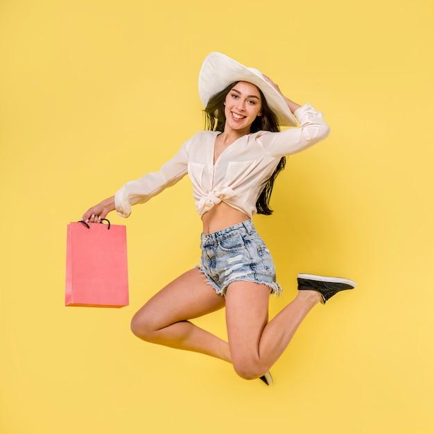 Feliz pulando fêmea no chapéu branco Foto gratuita