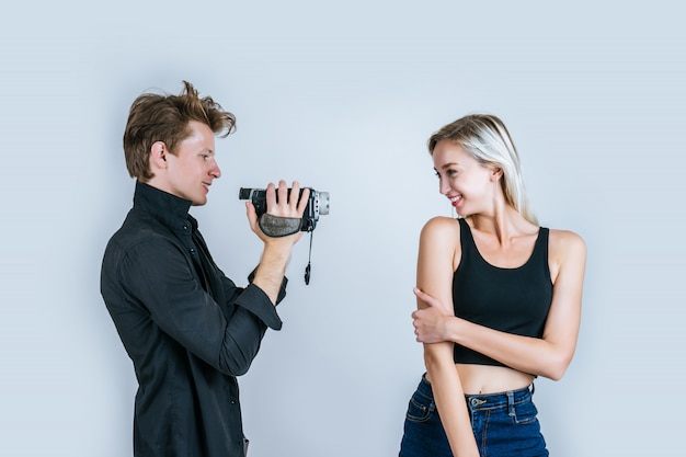 Feliz, retrato, de, par, segurando, câmera video, e, registro, clipe, vídeo Foto gratuita