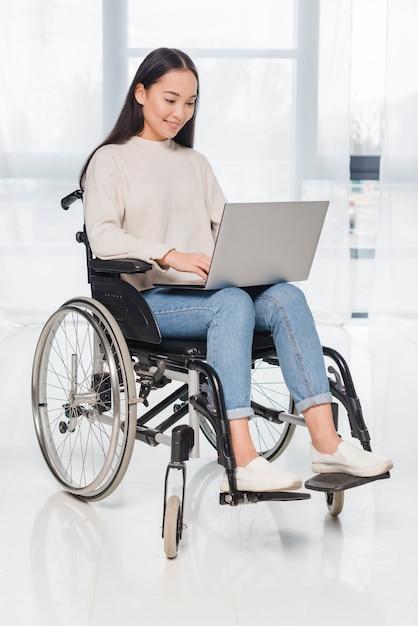 Feliz, retrato, de, sorrindo, incapacitado, mulher usa computador portátil Foto gratuita