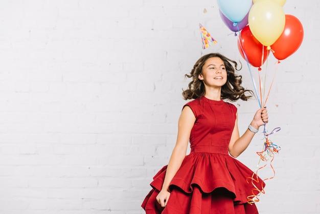 Feliz, retrato, de, um, menina adolescente, segurando, balões, em, mão saltando Foto gratuita