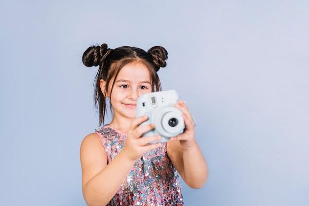 Feliz, retrato, de, um, menina, olhar, câmera instantânea, contra, azul, fundo Foto gratuita