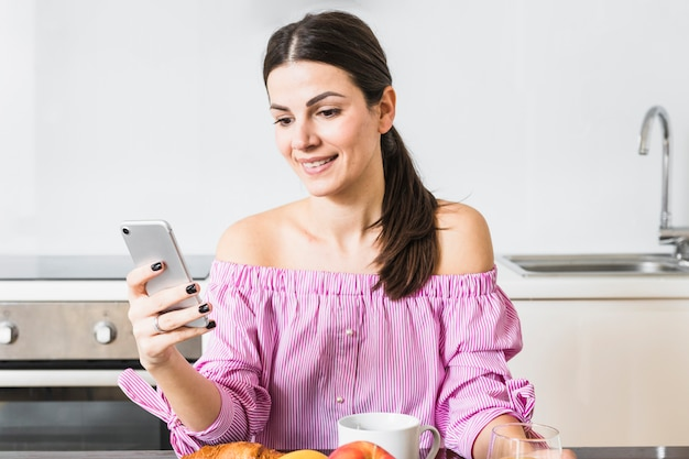 Feliz, retrato, de, um, mulher jovem, usando, cellphone, casa Foto gratuita