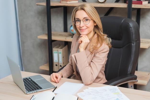 Feliz, retrato, de, um, sorrindo, jovem, executiva, sentar-se cadeira, em, local trabalho, com, laptop, e, papeis, ligado, tabela Foto gratuita