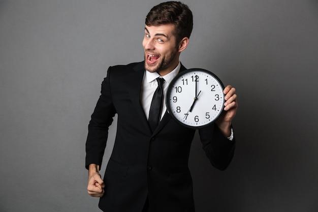 Feliz saiu barbudo homem de terno preto, segurando o relógio Foto gratuita
