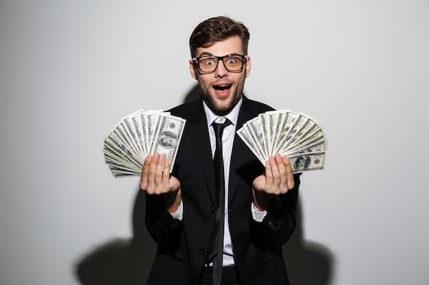 Feliz saiu homem de óculos e terno preto, segurando dois cachos de dinheiro Foto gratuita