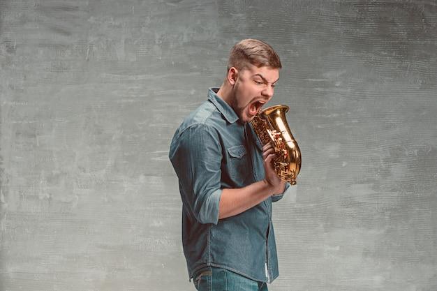Feliz saxofonista gritando com saxofone no studio cinza Foto gratuita